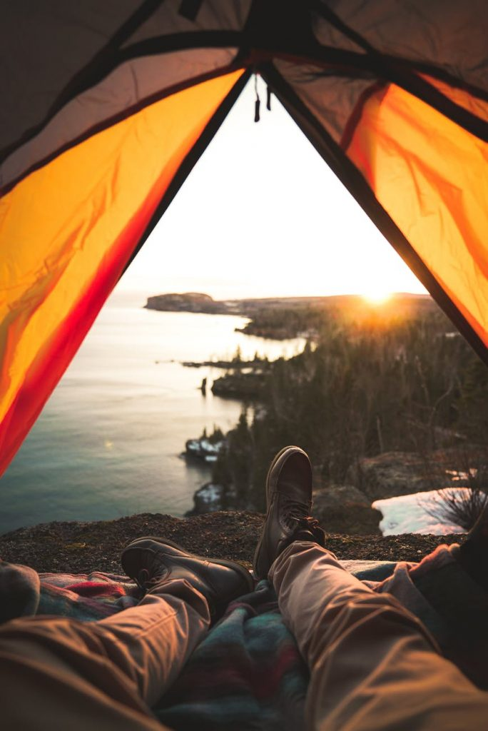 tourist lying in camping tent near shore